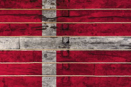 National flag  of  Denmark on a wooden wall background. The concept of national pride and a symbol of the country. Flags painted on a wooden fence with a rope