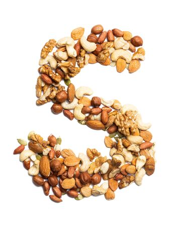 Letter S of the English alphabet from a mixture of hazelnuts, almonds, walnuts, peanuts, cashews, pumpkin seeds on a white isolated background. Food pattern made from nuts. Bright alphabet for shops.