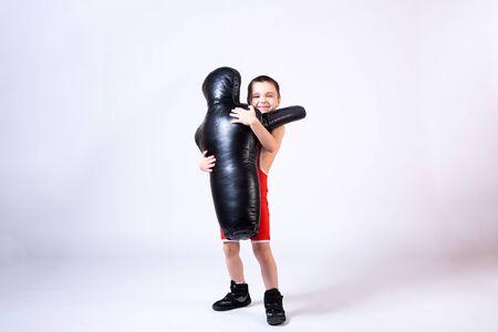 Chico alegre de deportes en medias de lucha libre y lucha libre sostiene un maniquí deportivo en sus manos para entrenar y manejar técnicas de diversas artes marciales sobre un fondo aislado de abeto. El concepto de entrenamiento de artes marciales para niños. Foto de archivo
