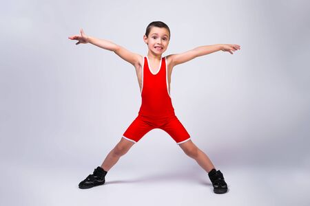 Little funny boy in a red sports ortsovskoy leotard and wrestling boots holds arms and legs in different directions and smiles at his achievements on a white isolated background.