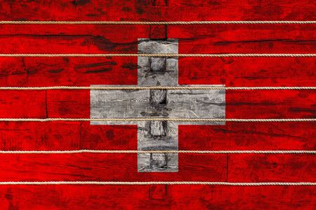National flag  of Switzerland on a wooden wall background. The concept of national pride and a symbol of the country. Flags painted on a wooden fence with a rope