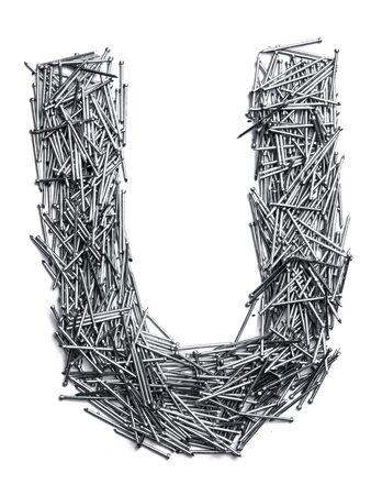 흰색 고립 된 배경에 작은 철 손톱에서 영어 알파벳의 문자 U. 패스너용 얇은 못의 산업 패턴. 디자인에 대한 밝은 숫자. 스톡 콘텐츠