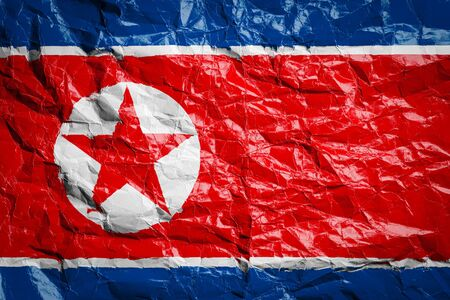 National flag of North Korea on crumpled paper. Flag printed on a sheet. Flag image for design on flyers, advertising.