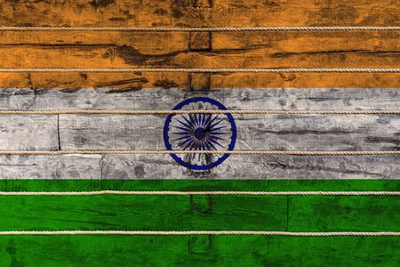 National flag of India on a wooden wall background. The concept of national pride and a symbol of the country. Flags painted on a wooden fence with a rope