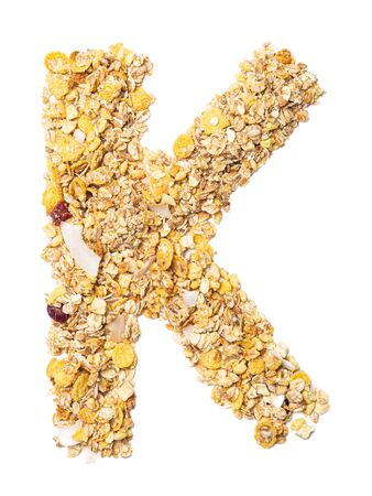 Letter K of the English alphabet muesli with coconut, berries, raisins, cereal and natural cereals  on a white isolated background. Food pattern made from granola. bright alphabet for shops.