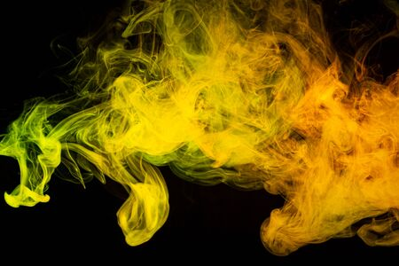 Cloud of  yellow and orange  smoke on a black isolated background. Background from the smoke of vape