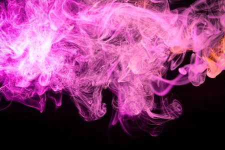 Colorful pink and red smoke  on a black isolated background. Background from the smoke of vape.  Abstract artwork.  Stock Photo