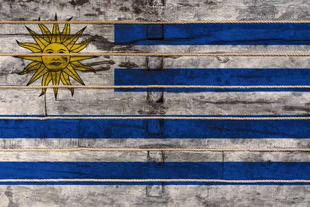 National flag  of Uruguay on a wooden wall background. The concept of national pride and a symbol of the country. Flags painted on a wooden fence with a rope