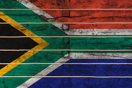 National flag of South African Republic on a wooden wall background. The concept of national pride and a symbol of the country. Flags painted on a wooden fence with a rope