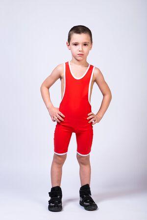 Un niño atleta en ropa deportiva y trajes de lucha está de pie con las manos a los lados y mirando a la cámara sobre un fondo blanco aislado. El concepto de un pequeño atleta luchador.