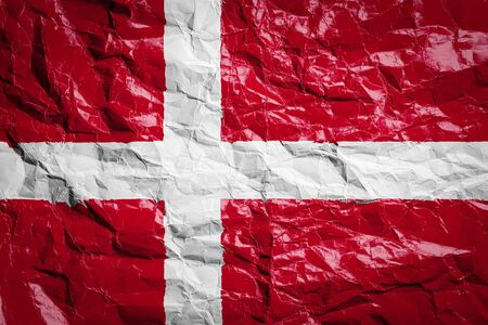 National flag of Denmark on crumpled paper. Flag printed on a sheet. Flag image for design on flyers, advertising.