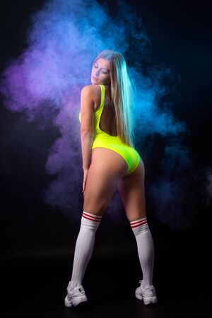 Young blonde woman in yellow swimwear posing against a background of  blue and pink  smoke from a vape on a black isolated background Imagens