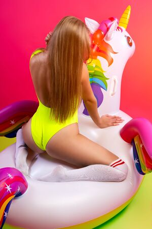 Summer Fashion beautiful woman in summer clothes having fun, smilling and posing with balloons On Unicorn Float on isolated pink background. Summer fashionable girl, pink and joyful mood. Reklamní fotografie