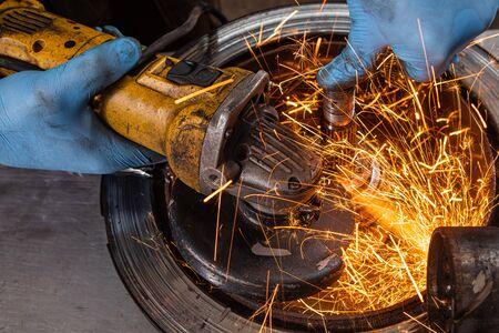Close-up of a man sawing   bearing metal brake disk with a hand circular saw, bright flashes flying in different directions, in the background tools for an auto repair shop. Work of auto mechanics. 写真素材
