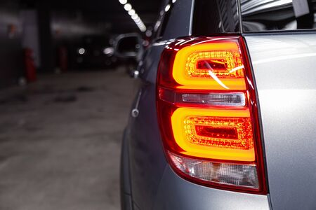 Close-up taillight of a new halogen silver crossover car. Exterior of a modern car. Close up detail on one of the LED lights modern car.