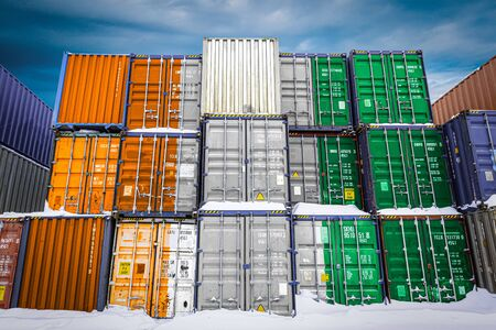 The national flag of Cote d'ivoire on a large number of metal containers for storing goods stacked in rows on top of each other. Conception of storage of goods by importers, exporters