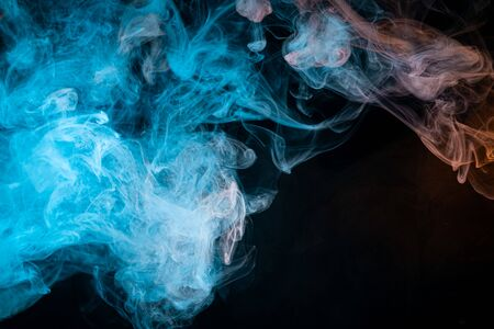 Thick colorful smoke of red, blue on a black isolated background. Background from the smoke of vape
