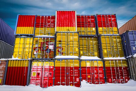 The national flag of Spain on a large number of metal containers for storing goods stacked in rows on top of each other. Conception of storage of goods by importers, exporters