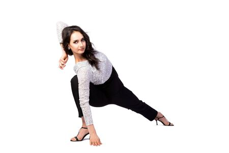 attractive woman in styling and bright makeup in a beautiful top with sparkles, black trousers and sandals stretched her leg on a white isolated background. Women's gymnastics, a demonstration of excellent stretching and twine anywhere. Unusual sports posing 写真素材