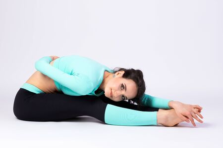 Attractive woman in styling and bright make-up in pants and top  stretches on the floor,  on a white isolated background. Pretty athlete for design and advertising.