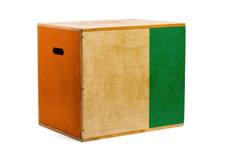 A wooden box for reliable shipment of various goods and cargo with the national flag of Cote d'ivoire on a white isolated background. The concept of export-import and national delivery of goods.  版權商用圖片