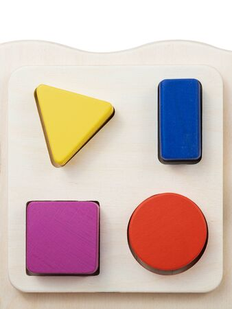 Photo of a wooden toy children's sorter with small wooden details in the form of geometric shapes (square, circle, rectangle , triangle), in different colors on a white isolated background