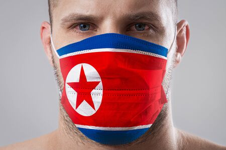 Young man with sore eyes in a medical mask painted in the colors of the national flag of North Korea