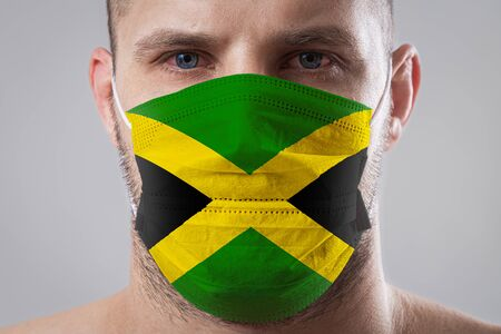 Young man with sore eyes in a medical mask painted in the colors of the national flag of Jamaica. Medical protection against airborne diseases, coronavirus. Man is afraid of getting the flu