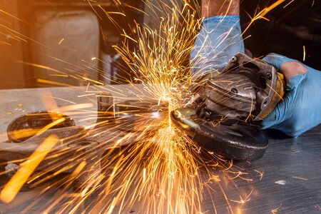 Close-up on the sides fly bright sparks from the angle grinder machine. A young male welder in a white working gloves grinds a metal product with angle grinder in the garage