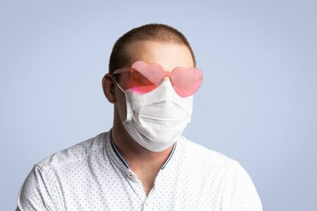 Positive young man wearing in pink heart sunglass and hygienic mask to prevent infection, airborne respiratory illness such as flu, 2019-nCoV on blue isolated background. Protection against contagious disease, coronavirus.