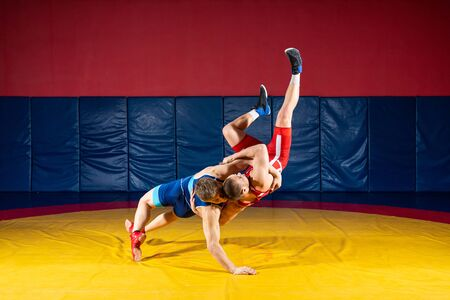 Two strong wrestlers in blue and red wrestling tights are wrestlng and making a  making a hip throw  on a yellow wrestling carpet in the gym. Young man doing grapple.  Banco de Imagens