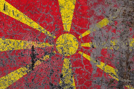 National flag of Macedonia on old peeling wall background.The concept of national pride and symbol of the country.