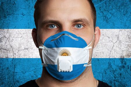 Young man with sore eyes in a medical mask painted in the colors of the national flag of Argentina. Coronovirus disease COVID-19 concept. Man is afraid of getting the flu