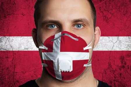 Young man with sore eyes in a medical mask painted in the colors of the national flag of Denmark. Coronovirus disease COVID-19 concept. Man is afraid of getting the flu 版權商用圖片
