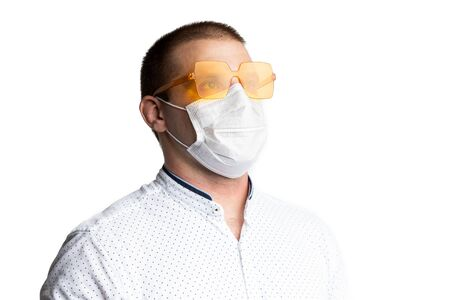 Portrait a man in a medical mask for surgeons and bright yellow glasses for healed from flu and coronavirus. The concept of a positive outlook on the pandemic of the Covid-19 in the world