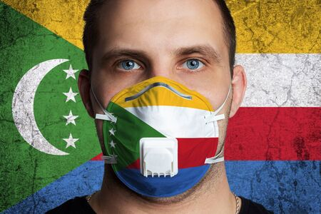 Young man with sore eyes in a medical mask painted in the colors of the national flag of Comoros. Coronovirus disease COVID-19 concept. Man is afraid of getting the flu
