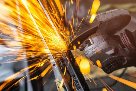Close-up on the sides fly bright sparks from the angle grinder machine. A young male welder in a working gloves grinds a old car with angle grinder in the garage