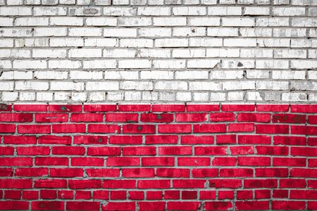 National flag of Poland  depicting in paint colors on an old brick wall. Flag  banner on brick wall background.