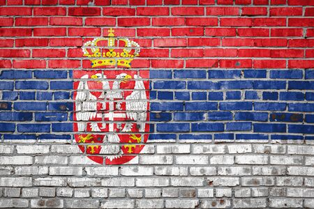 National flag of Serbia depicting in paint colors on an old brick wall. Flag  banner on brick wall background.