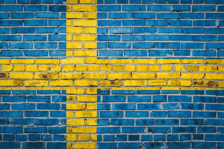 National flag of Sweden depicting in paint colors on an old brick wall. Flag banner on brick wall background.