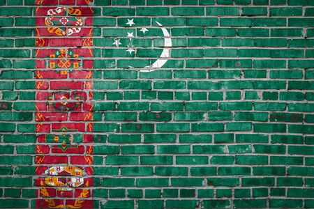 National flag of Turkmenistan  depicting in paint colors on an old brick wall. Flag  banner on brick wall background.
