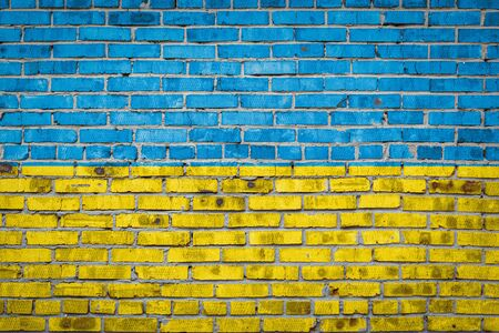 National flag of Ukraine  depicting in paint colors on an old brick wall. Flag  banner on brick wall background.