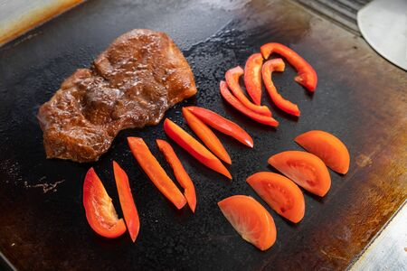 close-up cook fries on a large professional stove a large pickled piece of meat and pepper. The process of frying meat