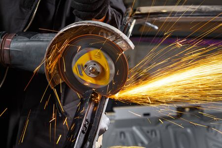 A close-up of a car mechanic using a metal grinder to cut a car silent block in a vise in an auto repair shop, bright flashes flying in different directions, in the background tools for an auto repair