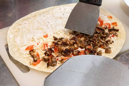 We cook shawarma step by step: a large round pita bread is spread with mayonnaise, cheese and tomato on a wooden board. Cooking fast food. 版權商用圖片