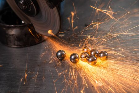 A young man welder in a white gloves grinder metal an angle grinder   in the   workshop. The concept of car repair and car repair shop. metal shiny ball bearings in  sparks fly to the side