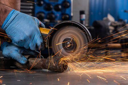 Close-up on the sides fly bright sparks from the angle grinder machine. A young male welder in a white working gloves grinds a metal product with angle grinder in the garage 版權商用圖片