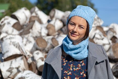 A cheerful attractive woman in stylish clothes (a dress with floral patterns, a knitted handmade hat and a coat) smiles, enjoys nature and sits on a mountain of birch logs. Village Life Concept