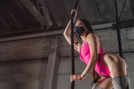 Creative portrait of a woman on an industrial theme.  Modern portrait of a woman in pink bodysuit and over the knee boots posing with ropes in a large industrial hangar. Stretch concept with canvases Stock Photo