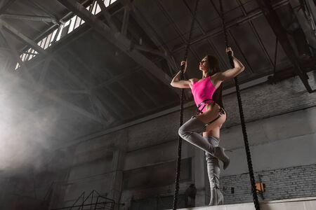 Creative portrait of a woman on an industrial theme. Modern portrait of a woman in pink bodysuit and over the knee boots posing with ropes in a large industrial hangar. Stretch concept with canvases